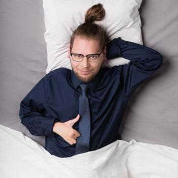 leżący mężczyzna wgranatowej koszuli, odkrawatem trzymający lewą ręke zagłową przykryty dopasa pościelą