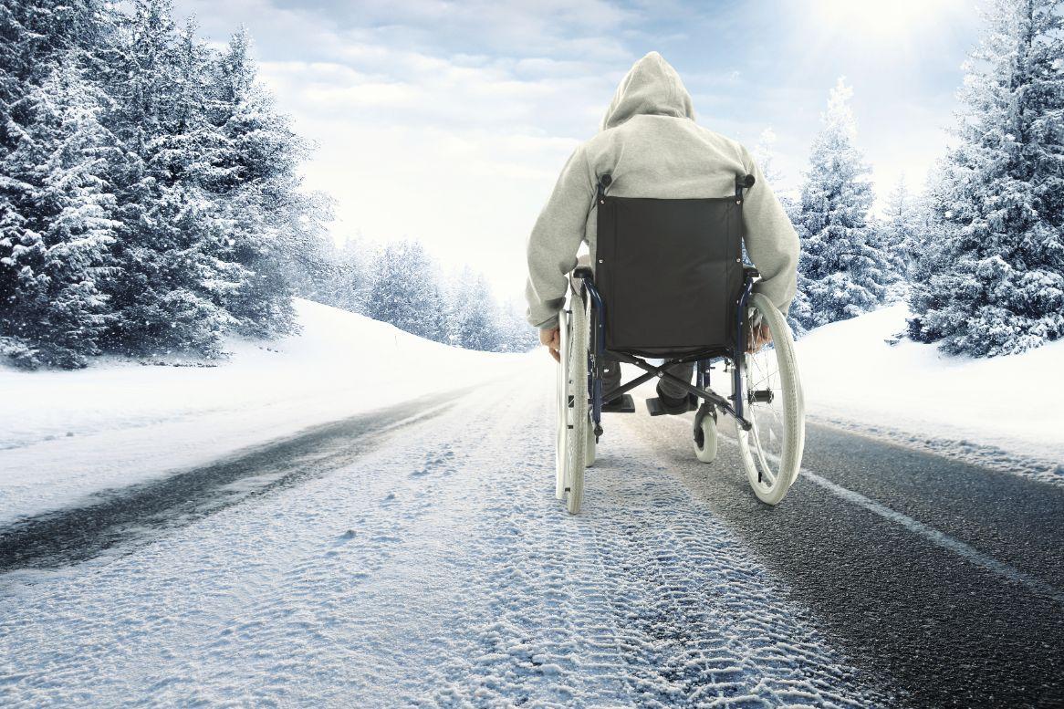 mężczyzna poruszający się na wózku inwalidzkim po nieośnieżonej drodze