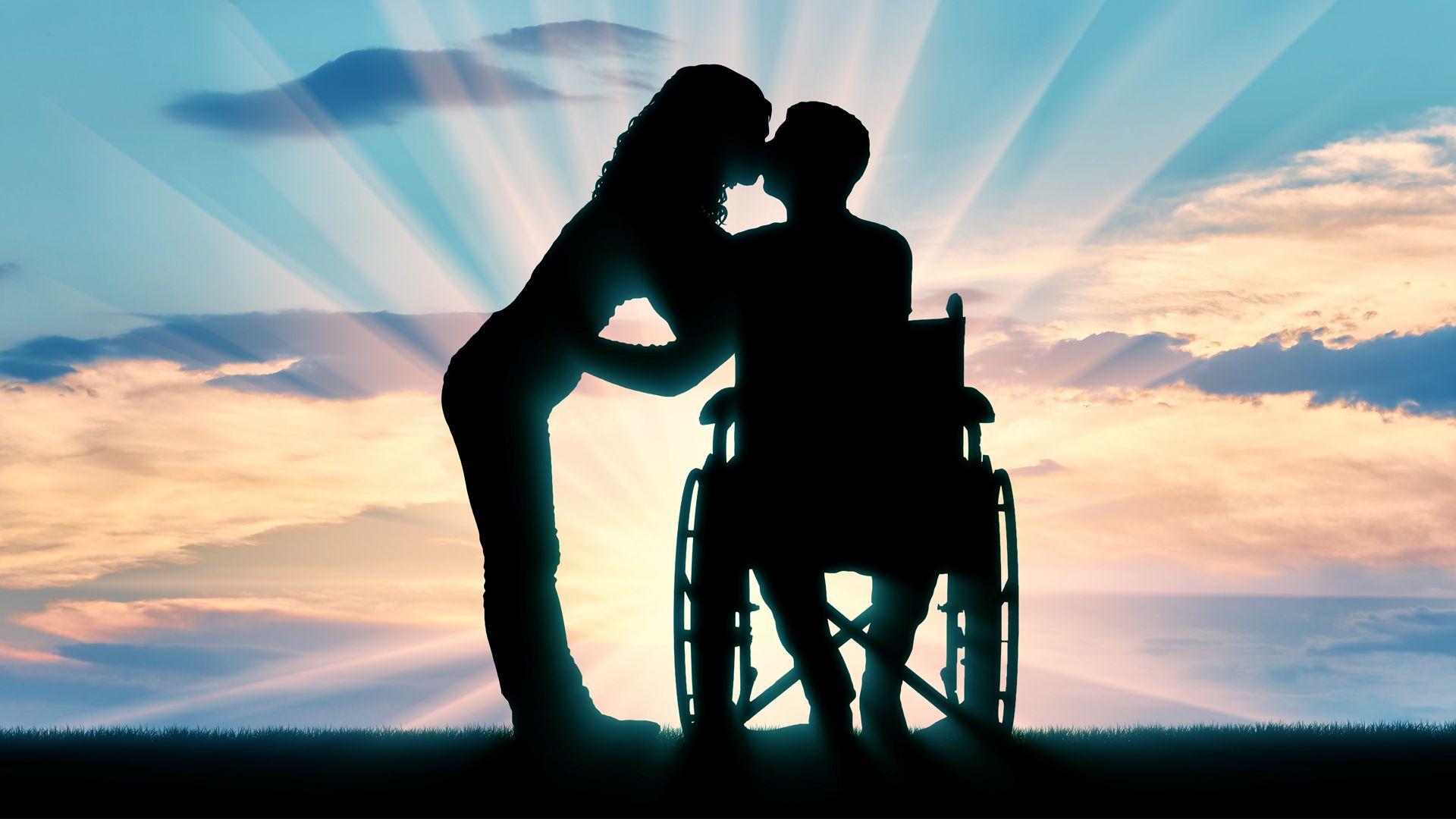 kobieta i mężczyzna na wózku dający sobie całusa
