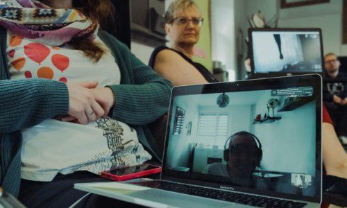 na ekranie laptopa mężczyzna z niepełnosprawnością w specjalnych okularczący się zdalnie za pomocą komunikatora intenetowego z koleżankami z pracyach, łą
