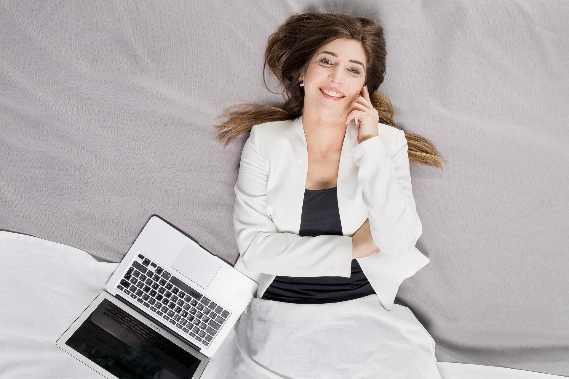 kobieta korzystająca z narzędzia do pracy zdalnej - komputer i smartfon