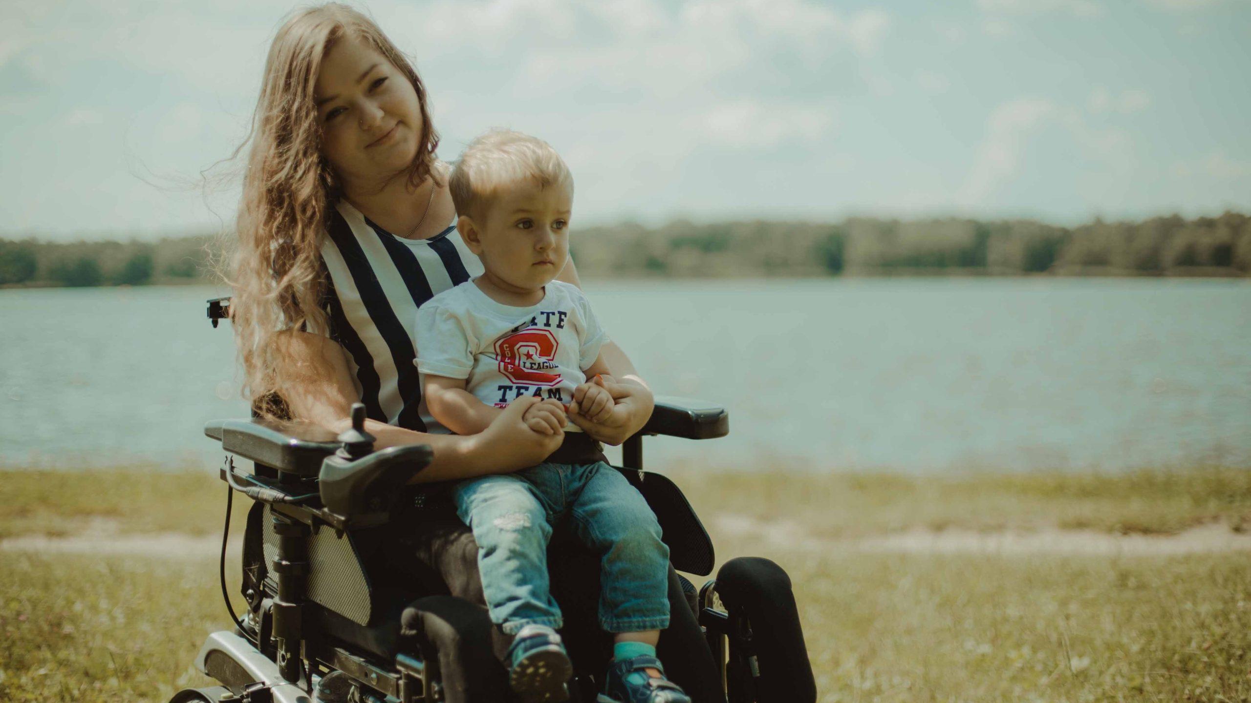 mama Nicole siedząca na wózku trzymająca na kolanach synka